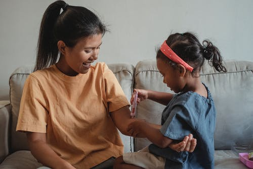Ethnic mother and daughter playing with toy syringe