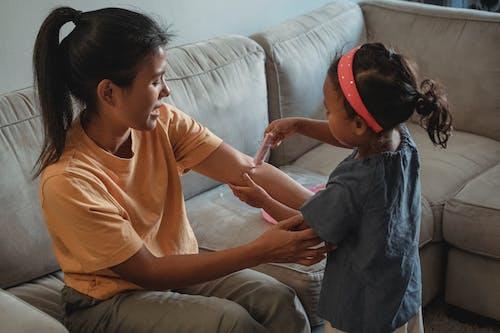 Азиатская девушка играет доктора с матерью