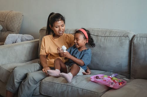 Cheerful ethnic woman sitting on couch with little girl playing with toy for checking pulse during game in living room