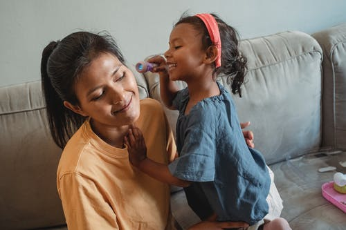 Cheerful Asian girl shining flashlight on ear of mother while doing check up during doctor game on sofa in living room