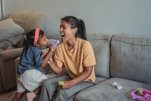 Счастливая азиатская мать играет доктора с дочерью