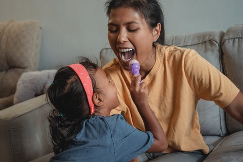 Cheerful ethnic little girl shining flashlight in mouth of positive mother while doing examination during game on sofa in apartment