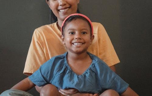 Opgetogen Aziatische Dochterzitting In Omhelzing Van Kropmoeder