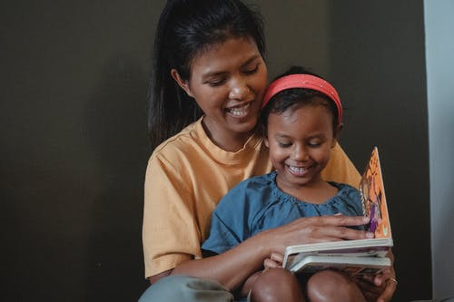 Positive Asian mother and daughter reading tale