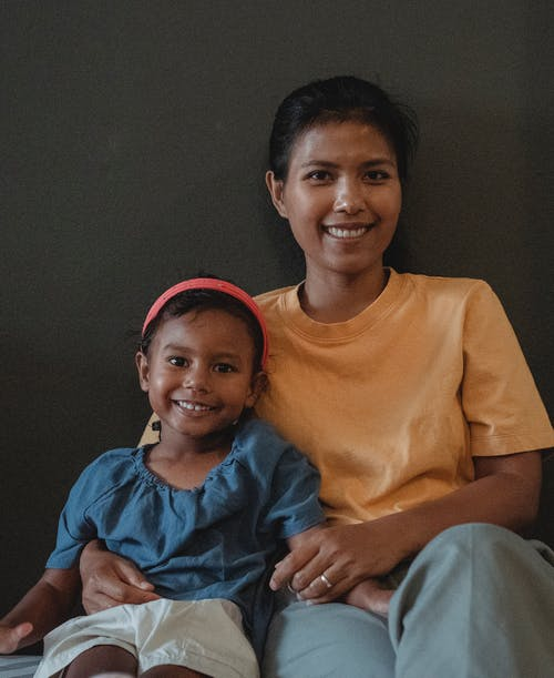 Smiling Asian mother and daughter sitting near wall at home