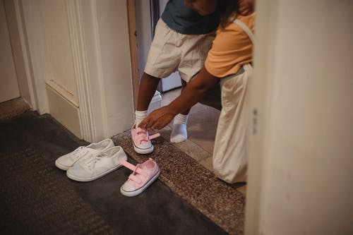 Unrecognizable ethnic mother helping anonymous girl to put on pink footwear while standing in doorway in apartment before going out