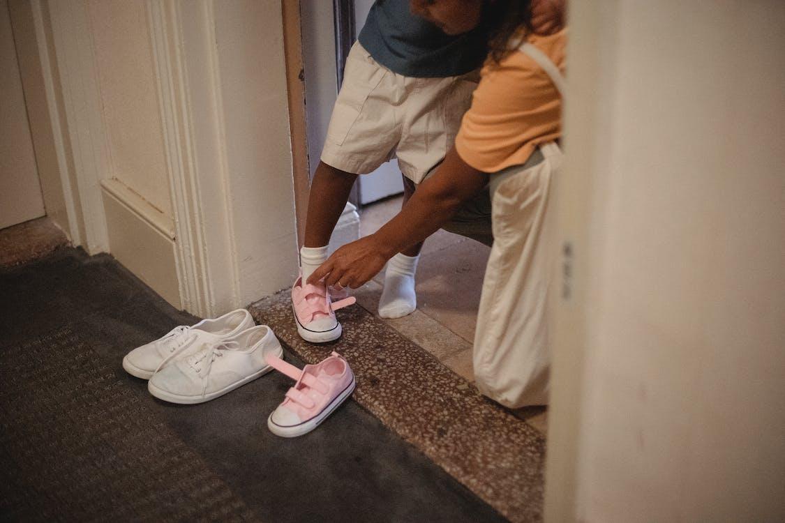 Crop Ethnische Frau Helfen Unerkennbaren Kind, Schuhe Anzuziehen