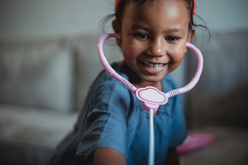 Delighted little ethnic kid with fake stethoscope leaning forward while playing doctor near couch on blurred background in living room