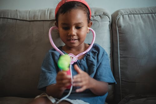 Cheerful Asian girl playing with stethoscope
