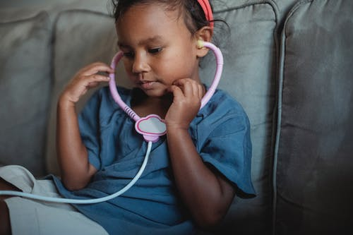 Side view of crop focused Asian kid wearing headband sitting on soft couch with toy stethoscope while playing doctor in cozy living room