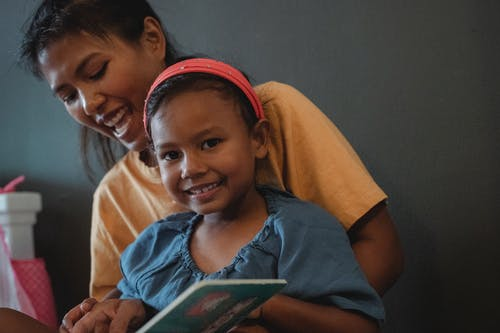 Cheerful ethnic mother hugging positive little girl looking at camera while reading book near black wall during weekend in apartment