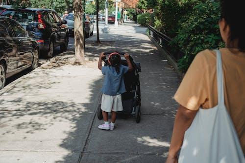 Unrecognizable ethnic girl pushing carriage on walkway