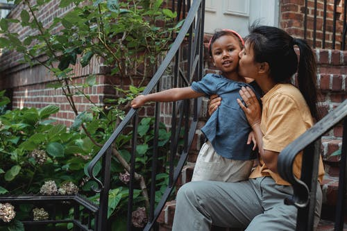 Tender ethnic mother hugging and kissing little girl while sitting on stairs of house with metal railing near green plants on terrace