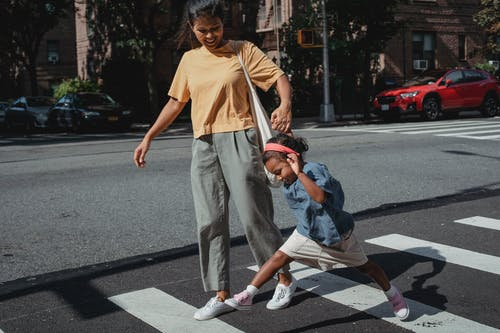 Playful Asian mother and daughter crossing road