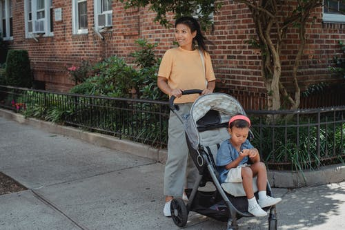 Happy Asian mother with cute little daughter on baby carriage
