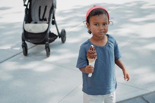 Cute Asian little girl eating chocolate sweet ice cream