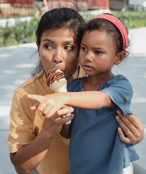 Asian mother with daughter eating ice cream together