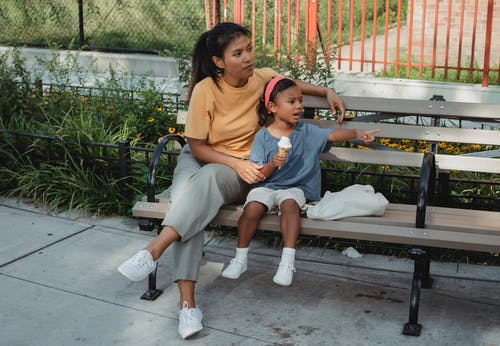 Asian mother and kid sitting on bench on street in sunny day