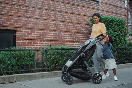 Full length of Asian mom with small girl strolling on footpath with stroller near green hedge in city