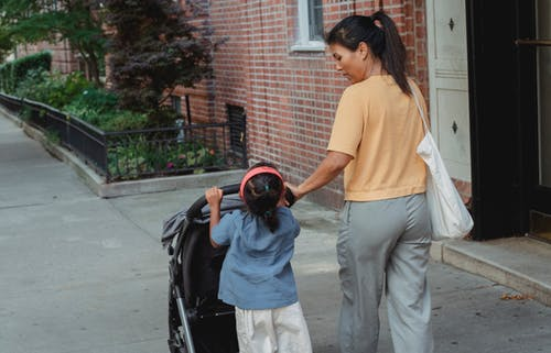 Back view of ethnic woman carrying stroller with little girl on sidewalk of street
