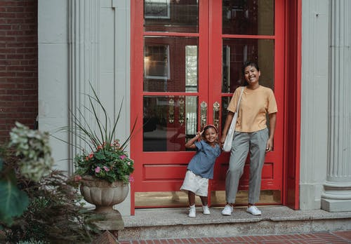 Cheerful Asian mother and daughter standing near entrance of house