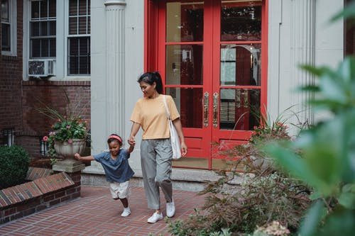 Full body of positive Asian girl running while holding hand of mom walking from home