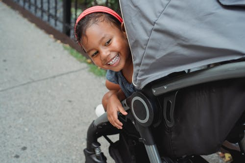 Cute ethnic girl smiling brightly in stroller