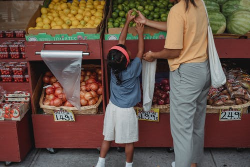 Ethnic woman choosing fruits with daughter in market