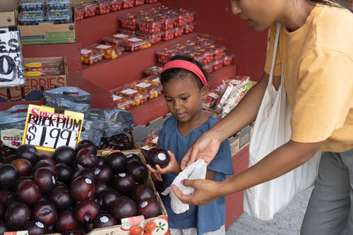 Ethnic girl choosing fruit in market with mother