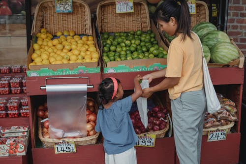 Back view of Asian girl picking ripe limes from box to eco friendly bag while shopping with mother in market