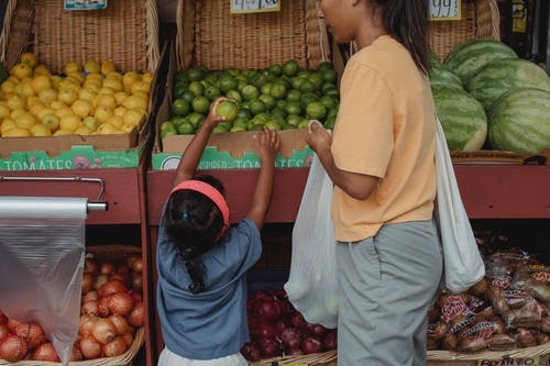 Ethnic girl choosing fruit from box in bazaar with mother