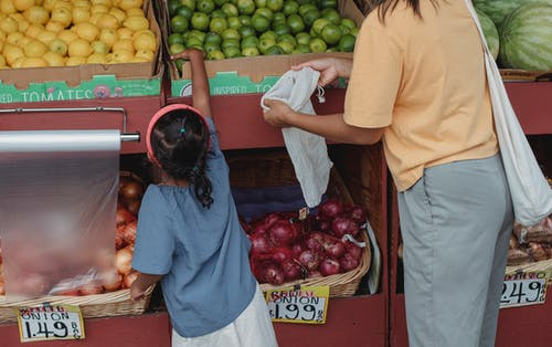 Back view of crop anonymous mother with reusable bag and girl choosing limes from box