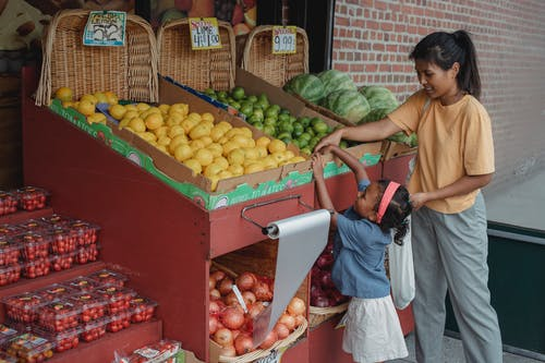 Small ethnic girl taking fruits from box with mother