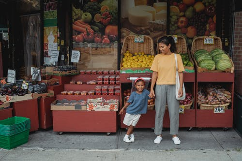 Happy Asian mother and daughter standing near street market stall