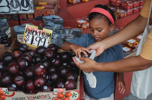 Asian girl and mother buying sweet plums in street market