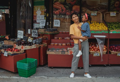 Content Asian mother holding daughter on hands near market stall