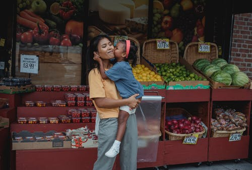 Asian girl kissing mothers cheek in street food market