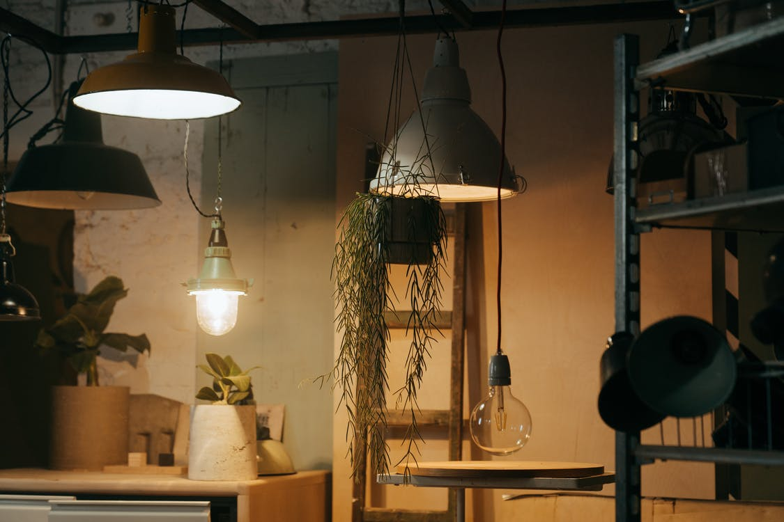 Silver Pendant Lamp Turned on Near Brown Wooden Table