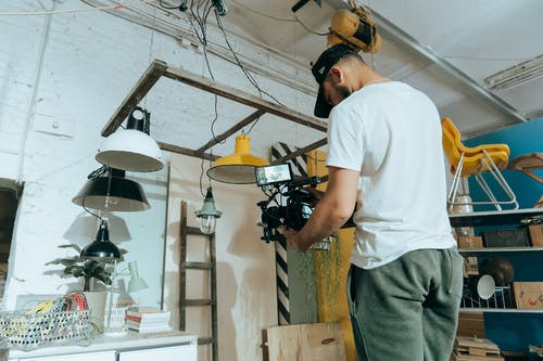 Man in White Crew Neck T-shirt and Gray Pants Holding Black and Yellow Power Tool