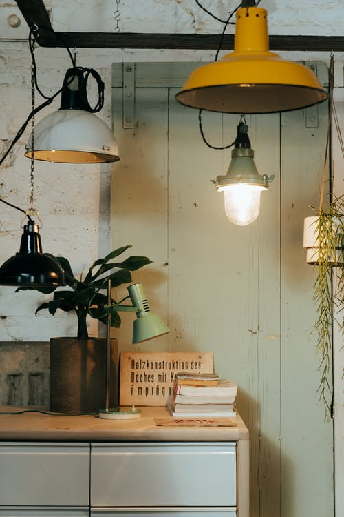 White Pendant Lamps Turned on Near Brown Wooden Shelf