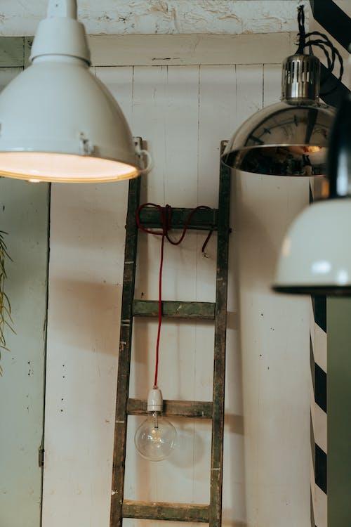 White Pendant Lamp Turned on Near Brown Wooden Shelf