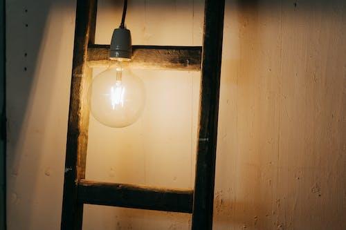 White Light Bulb Turned on Near Brown Wooden Frame
