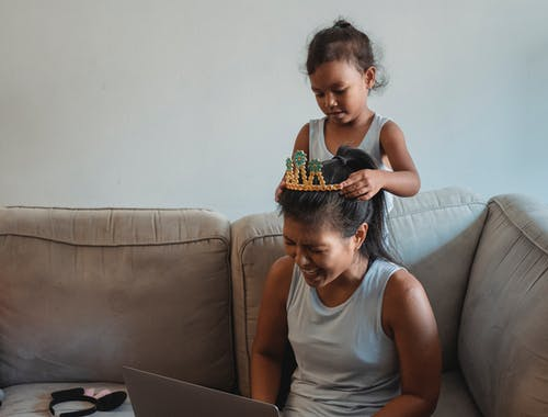 Adorable Asian girl putting crown on laughing mothers head siting on cozy couch and working on laptop at home