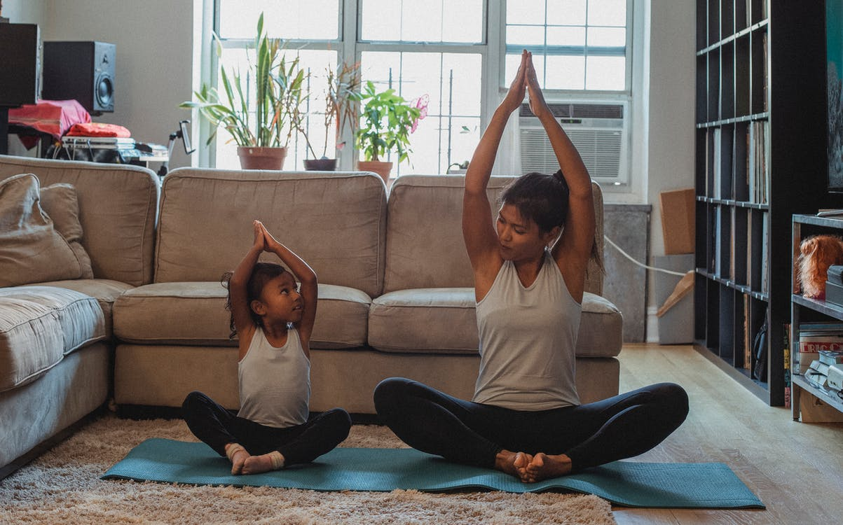 Full body content fit Asian woman and daughter in activewear sitting in Lotus Pose with arms raised and looking at each other while practicing yoga in cozy living room