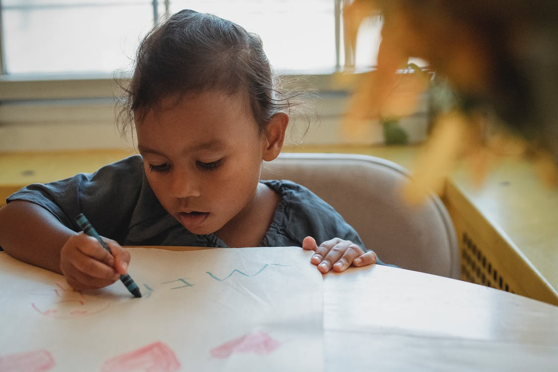 Focused Asian girl drawing with crayons at home