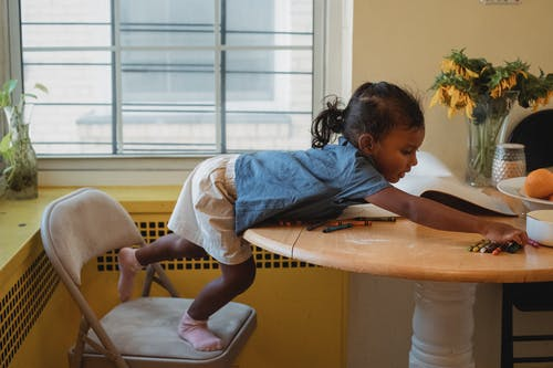 Adorable Asian girl painting with crayons on table