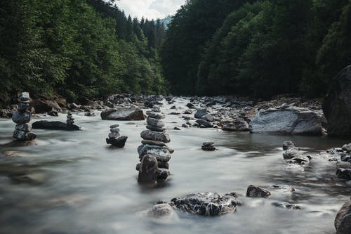 Stone pyramids in streaming river among lush forest