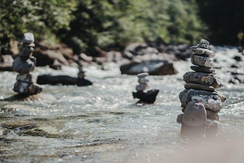 Balanced rock zen stack in flowing river