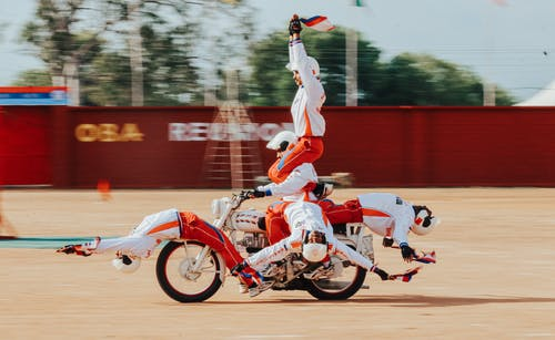 Man in White and Red Jersey Shirt Riding Red Motorcycle