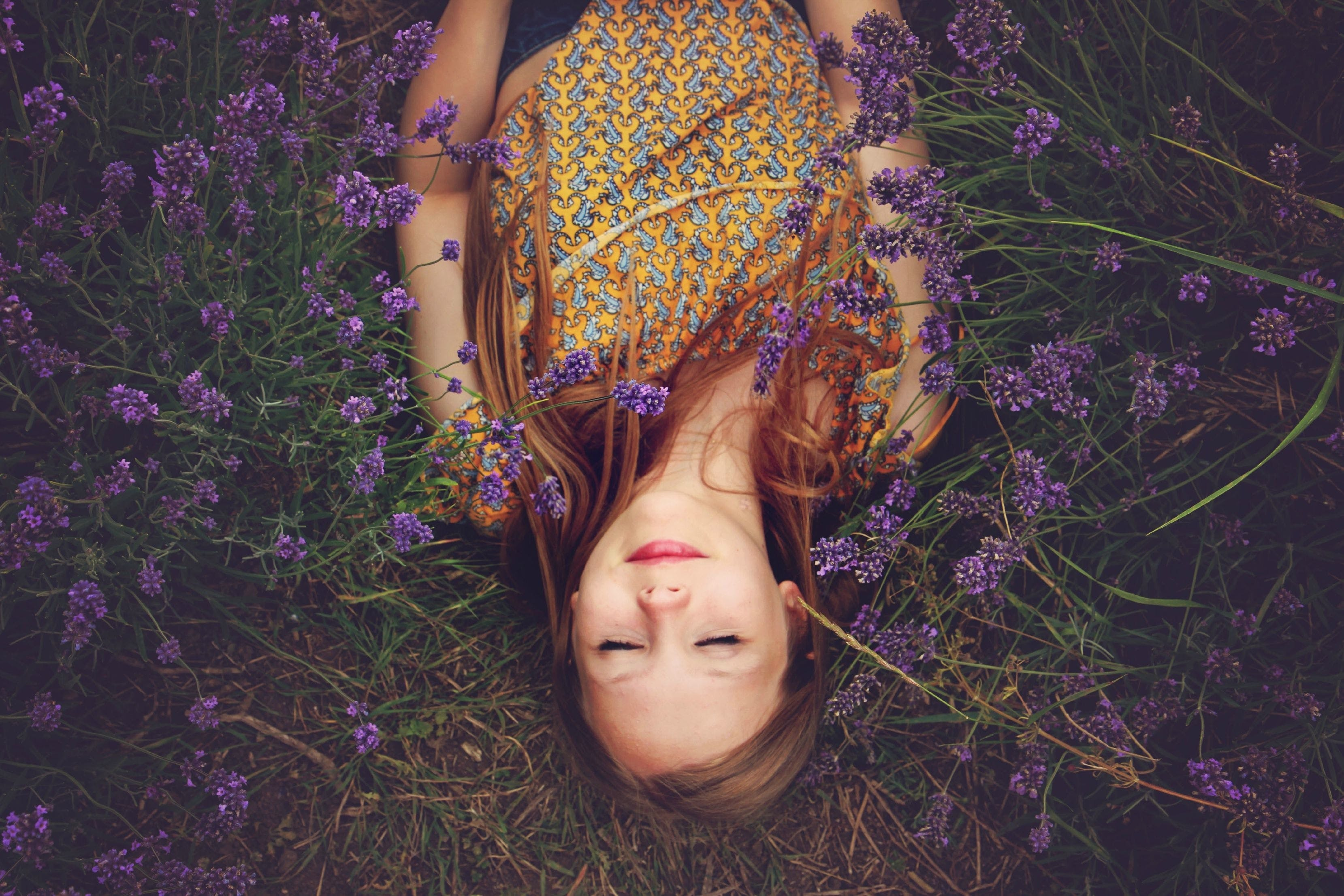 Woman in Yellow Tank Top Lying on Grass Beside Purple Leaf Plant during Daytime